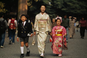 A Japanese mother and her children wearing traditional kimonos.